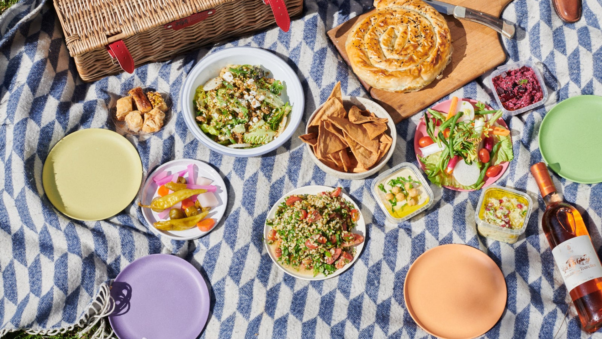 This is a photo of a picnic box spread from Arabica, London, including hummus, beetroot borani and summer freekeh salad.