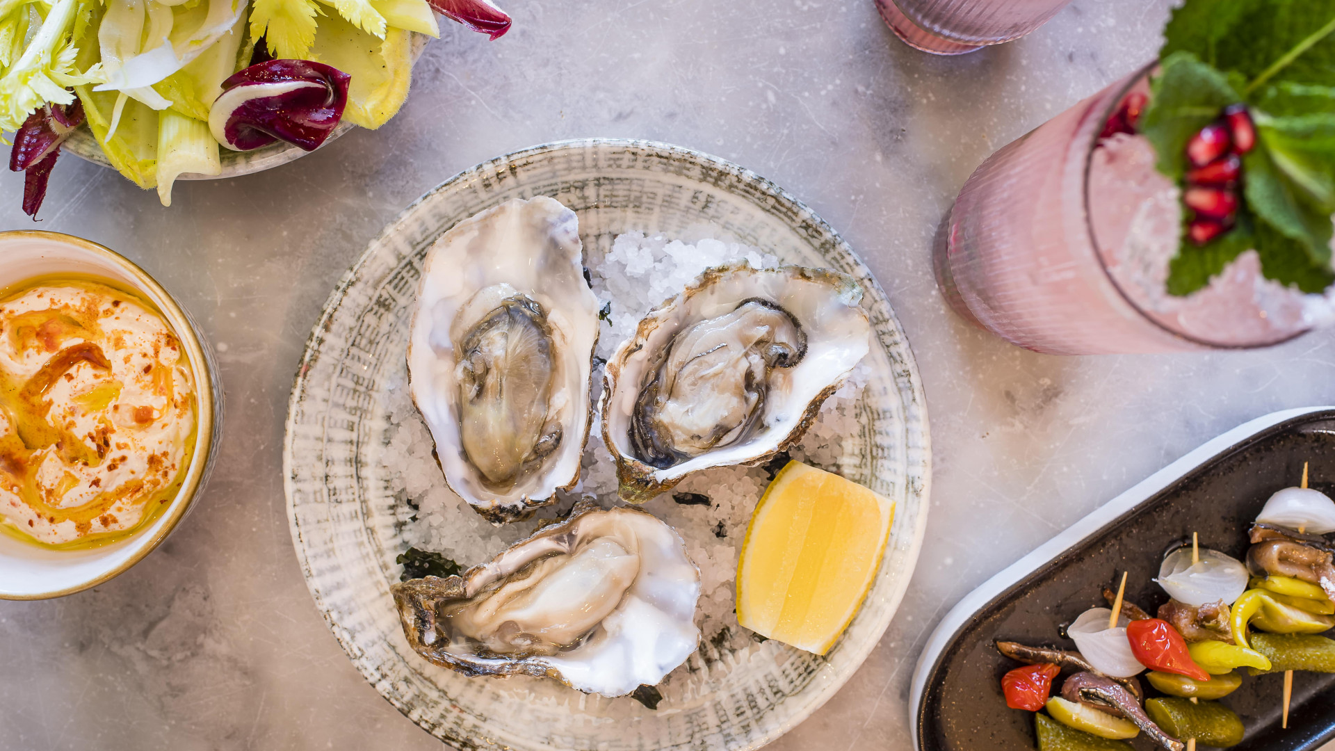 This is a photo of oysters, side dishes and a cocktail at Burnt Orange in Brighton.
