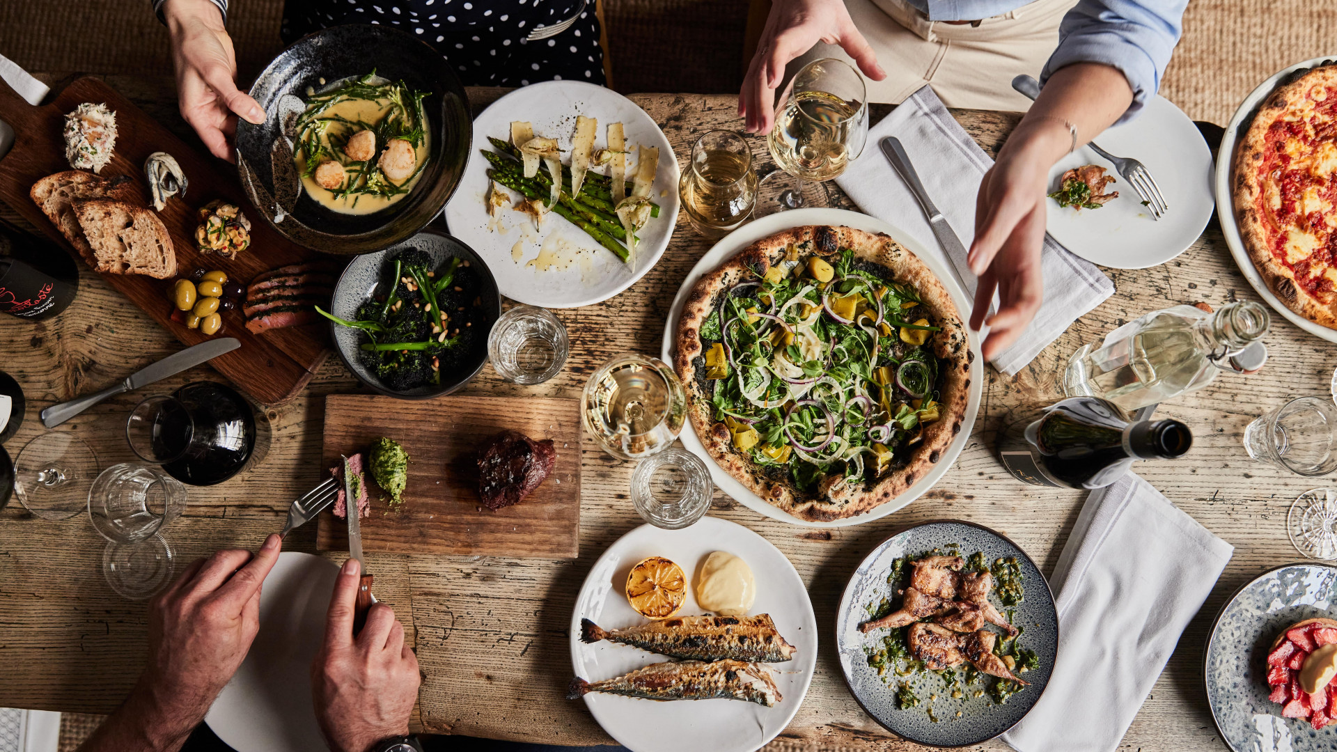 This is a photo of people enjoying a food spread of pizza, asparagus, fish, bread, olives and wine at the Wilding restaurant in Oxford.