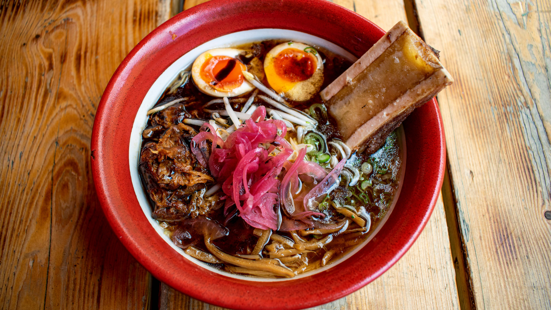 This is a photo of the Bone Daddies and Black Bear collaboration, which includes Bone Daddies beef bone broth, Black Bear beer braised brisket, bone marrow, pink pickled onions, bamboo shoots, beansprouts and a soy Clarence Court egg.